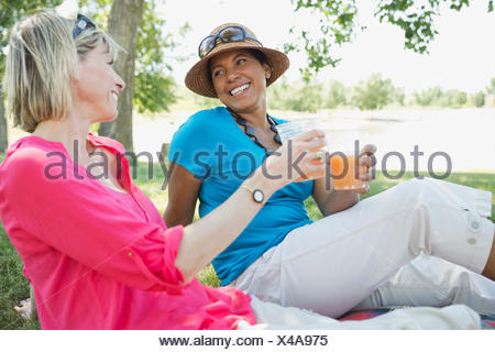 Middle-aged girl friends having a drink outdoors - Stock Photo