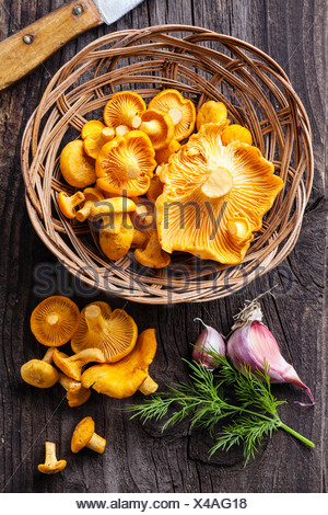 Raw chanterelles in basket on wooden texture - Stock Photo