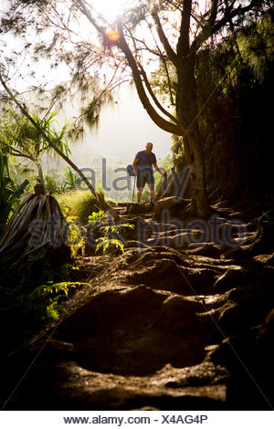 A hiker along the Kalalau Trail on the Na Pali Coast of Kauai. - Stock Photo