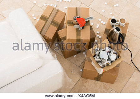 Duct tape boxes crockery kettle and cups beside sofa wrapped in plastic sheet overhead view - Stock Photo