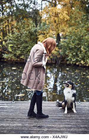 Woman with her dog on jetty in autumn - Stock Photo
