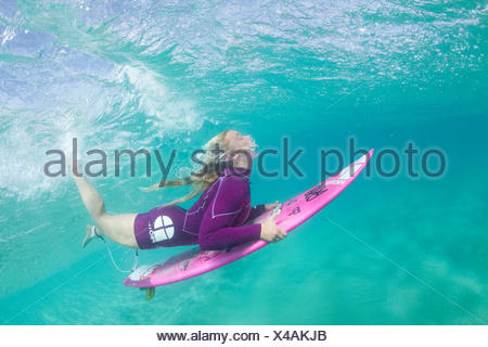 Underwater photo of a blonde surfer girl with a short wetsuit duck diving under a wave - Stock Photo