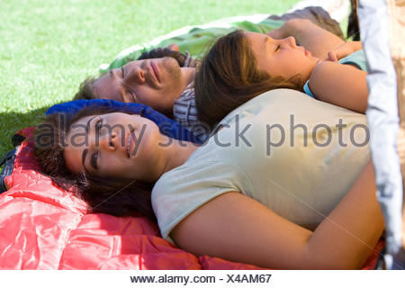 Family lying on sleeping bags in tent entrance on garden lawn, father and children (7-9) sleeping, mother daydreaming, side view - Stock Photo