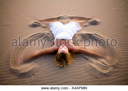 A woman in white making a sand angel on the Stovepipe Wells Dunes in Death Valley, California. - Stock Photo