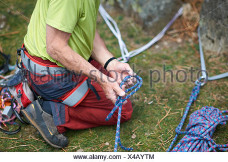 Cropped view of rock climber preparing climbing rope - Stock Photo