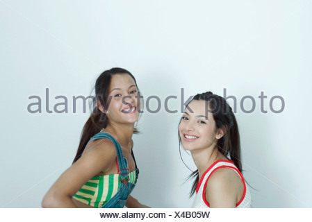 Two young female friends, smiling at camera, portrait - Stock Photo