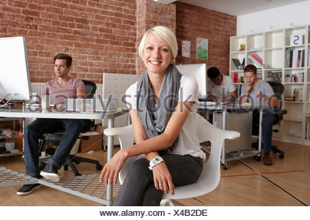 Portrait of mid adult woman sitting on chair in creative office - Stock Photo