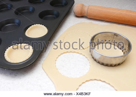 Lining a bun tin with circles of rolled out pastry to make mince pies, with a rolling pin on the worktop - Stock Photo