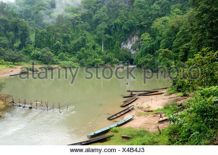Simple long boats of the Laotian fishermen at the entrance of the 7.5 km long cave of Tham Kong Lor, in the dense tropical rain - Stock Photo