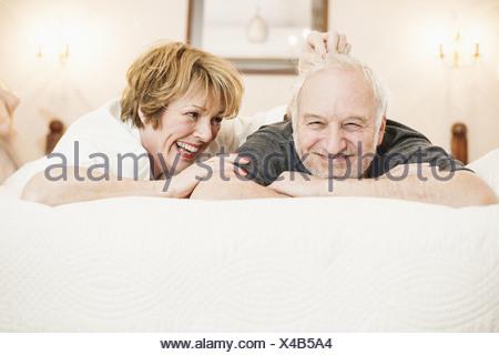 Couple lying on bed, portrait - Stock Photo