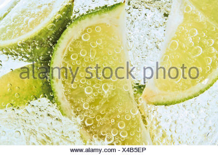 Lime slices in a fizzy drink, close-up - Stock Photo