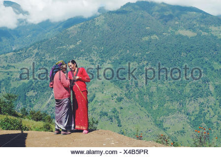 Nepal, Women standing and talking in mountains - Stock Photo