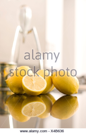 Lemons and an Alessi Juicy Salif Juicer by Philippe Starck in the background - Stock Photo