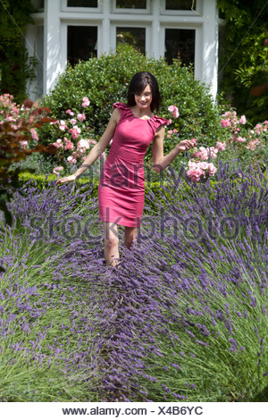 Woman walking in field of flowers - Stock Photo
