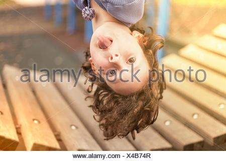 Girl in playground hanging upside down looking at camera sticking out tongue - Stock Photo