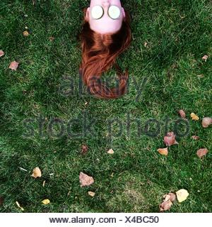 Teenage girl lying on the grass, with slices of cucumbers covering her eyes - Stock Photo