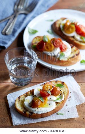 Still life of bruschetta with roasted cherry tomatoes, buffalo mozzarella, fresh oregano and pepper - Stock Photo