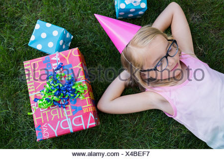Overhead view girl party laying birthday gifts grass - Stock Photo