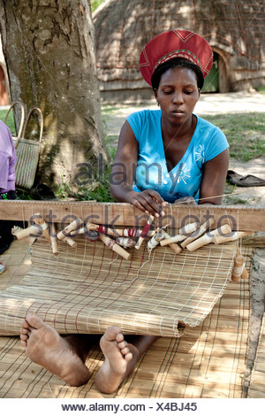African woman dressed in traditional clothing sits on floor, weaving a straw mat - Stock Photo