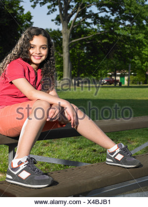 A girl sat on a bench - Stock Photo
