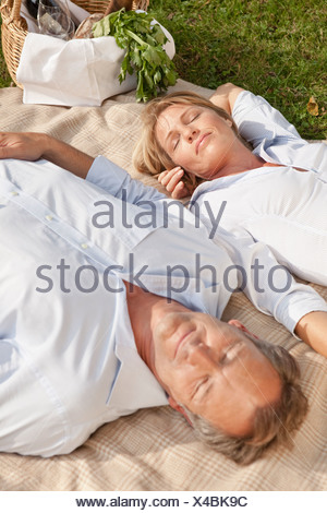 Middle aged couple on a picnic blanket - Stock Photo