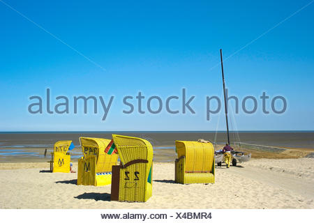roofed wicker beach chairs and catamaran on the beach Sahlenburg, Germany, Lower Saxony, Cuxhaven - Stock Photo