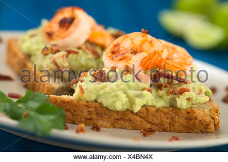 Wholegrain toast bread slices with guacamole, fried shrimp and fried bacon pieces served on plate on blue wood (Selective Focus, Focus on the front of the shrimp in the middle) - Stock Photo