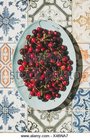 Fresh ripe sweet cherries in blue plate over colorful oriental ceramic tiles background, top view, flat lay. Summer food concept - Stock Photo