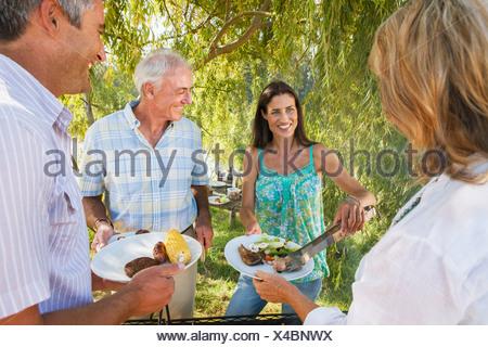Adult Family Group Cooking Barbeque In Countryside - Stock Photo