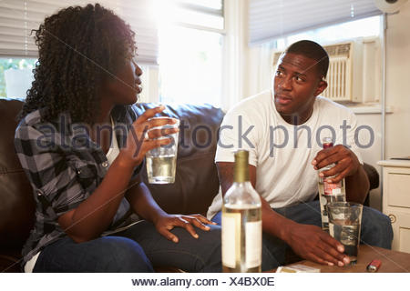 Couple Sitting On Sofa Drinking Alcohol And Arguing - Stock Photo