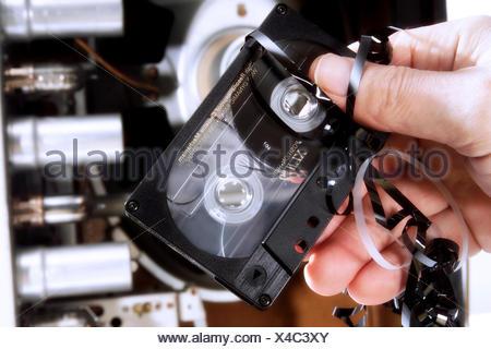 Hand holding audio cassette tape, tape jam (jammed tape) - Stock Photo
