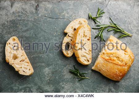 Sliced bread Ciabatta and rosemary on gray stone slate background - Stock Photo