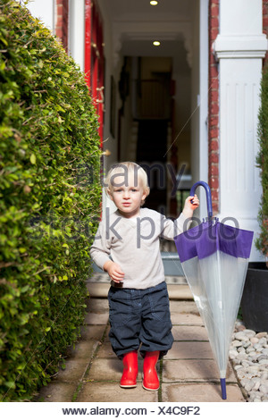 Little boy standing on front garden path with umbrella and rubber boots - Stock Photo