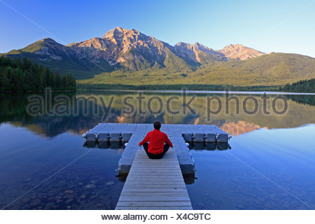 Middle age male meditating on dock at Pyramid Lake, Jasper National Park, Alberta, Canada. - Stock Photo