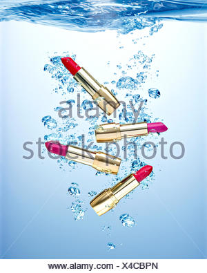 Four waterproofed lipsticks under water - Stock Photo