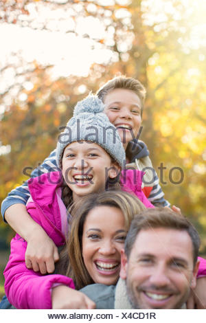 Portrait enthusiastic family hugging outdoors - Stock Photo