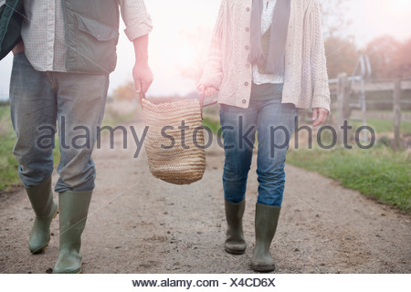 couple carrying basket in countryside - Stock Photo