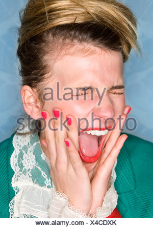 Young woman screams hands to face - Stock Photo