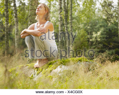 Woman crouching on a large rock in forest with eyes closed. - Stock Photo