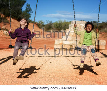 Two girls sitting on a swing - Stock Photo