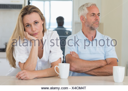 Fed up woman sitting at the counter with her partner - Stock Photo