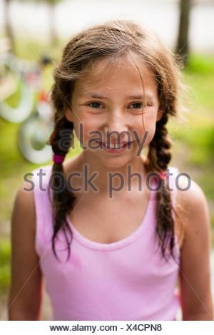 High angle portrait of young girl with pigtails looking at camera smiling - Stock Photo