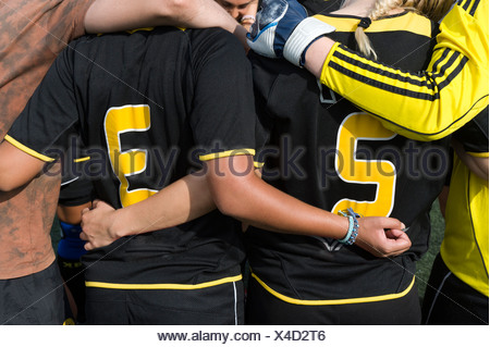 Close-up midsection of football players with arms around before the game - Stock Photo