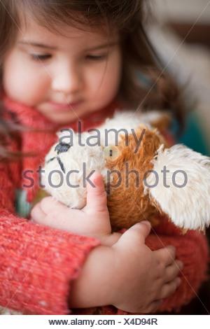 Little girl hugging toy dog - Stock Photo