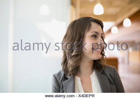 Portrait smiling brunette businesswoman looking away - Stock Photo