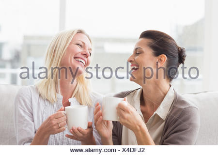 Women gossiping while having coffee in living room - Stock Photo