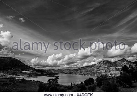 Scenic View Of Lake And Mountains Against Cloudy Sky - Stock Photo
