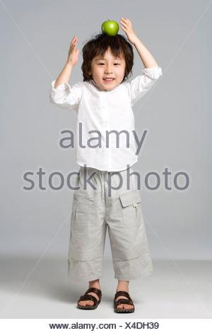 Boy balancing an apple on his head - Stock Photo