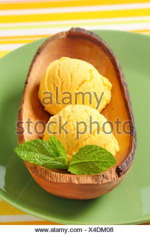 Yellow ice-cream in wood bowl - Stock Photo