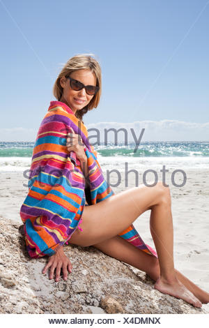 Woman sitting on the beach wrapped in a beach towel - Stock Photo